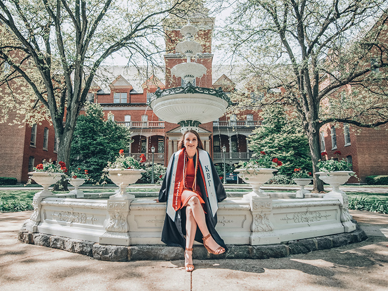 Lauren Grzyboski wearing graduation garb and posing in front of Shippensburg University's Old Main fountain