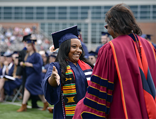 Female student preparing to hug Shippensburg University president Laurie Carter at commencement ceremony.