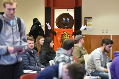 Reese's Character waves to room full of students