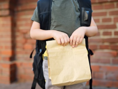 young student wearing backpack holds bagged lunch