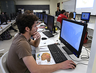Man sitting at computer in lab while other students and professor work in background.