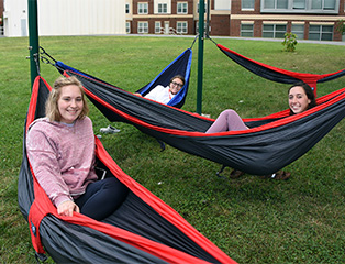 Female students smiling in hammocks with residence halls in the background.